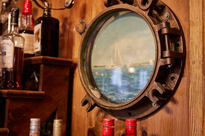 A porthole hanging on the wall of the focsle with a painting inside it
