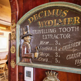 An antique wooden costing sign for Decimus Woolmer Travelling Tooth Extractor